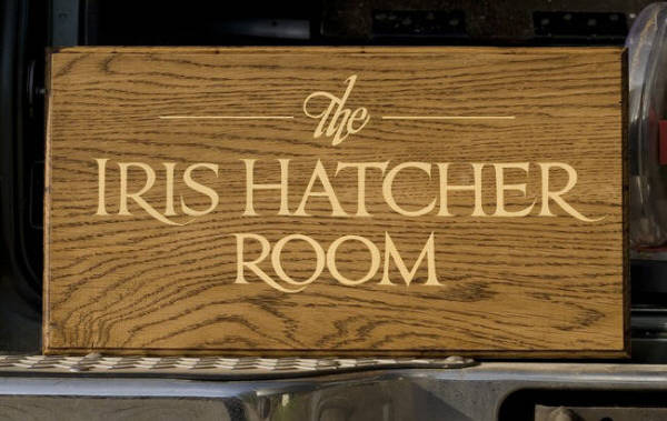 The Iris Hatcher Room, freehand Trajan lettering on oak.